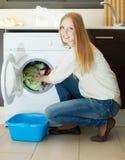 Langhaarige Frau, die zu Hause Waschmaschine verwendet Stockbild