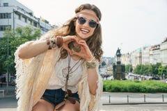 Langhaarige Hippie-aussehende junge Dame, die Herz zeigt, formte Hände Lizenzfreies Stockbild
