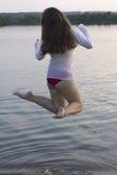 Langhaarige weiße Frau springen in Wasser Stockbilder