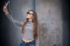Langhaariger Brunette, der selfie gegen Metallrostige Wand nimmt Stockfoto