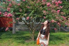 Langhaariger brunette kaukasischer weiblicher Tourist, der mit rosa Blüte aufwirft stockfotografie