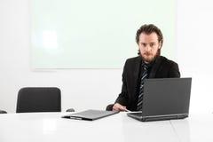 Langhaariger Geschäftsmann, der in einer Chefetage sitzt Stockbild