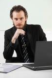 Langhaariger Geschäftsmann, der in einer Chefetage sitzt Lizenzfreies Stockfoto