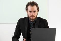 Langhaariger Geschäftsmann, der in einer Chefetage sitzt Stockfotos