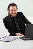 Langhaariger Geschäftsmann, der in einer Chefetage sitzt Lizenzfreies Stockbild