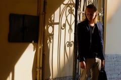 Langhaariger junger Mann nahe Gusseisenzaun in der Stadt stockfoto