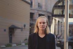 Langhaariger junger Mann nahe Gusseisenzaun in der Stadt stockfotos