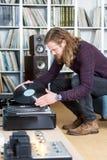 Langhaariger Mann, der eine Langspielplatten-Aufzeichnung auf die Drehscheibe setzt Lizenzfreie Stockfotografie