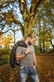 Langhaariger Mann, der in einem Herbstpark aufwirft stockfoto