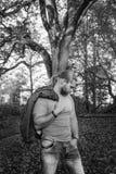 Langhaariger Mann, der in einem Herbstpark aufwirft stockbilder