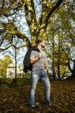 Langhaariger Mann, der in einem Herbstpark aufwirft lizenzfreie stockfotos