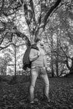 Langhaariger Mann, der in einem Herbstpark aufwirft lizenzfreies stockfoto