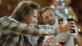 Langhaariger Mann, der seiner Großmutter seinen Smartphoneschirm durch Weihnachtsfamilientabelle zeigt stock video footage