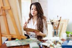 Langhaariger weiblicher Künstler malt Bild stockfotos