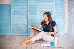 Langhaariger weiblicher Künstler malt etwas auf Segeltuch lizenzfreies stockfoto