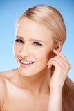 Langhaariges blondes Frauenporträt auf Blau Stockbilder