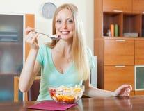 Langhaariges blondes Mädchen, das Obstsalat im Haus isst Stockbild