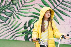 Langhaariges blondes Mädchen in einer gelben Strickjacke und in einer gelben Jacke lizenzfreies stockbild