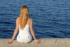 Langhaariges Mädchen, das durch das Meer sitzt Stockfotografie
