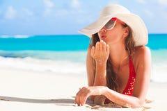 Langhaariges Mädchen im Bikini und in Strohhut, die einen Kuss auf tropischem karibischem Strand durchbrennen Stockbild