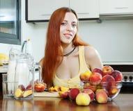 Langhaariges Mädchen im gelben Kochen mit Pfirsichen Stockfotos
