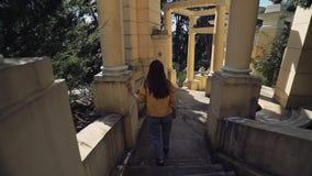 Langhaariges Mädchen steigt die Schritte der alten Laube entlang den Spalten ab stock video footage
