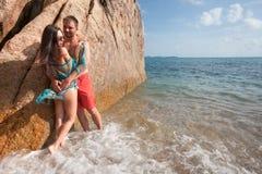 Langhaariges Mädchen und Kerl nahe auf großem Stein am Hintergrund von azurblauem Meer Lizenzfreie Stockfotografie