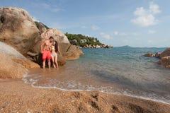 Langhaariges Mädchen und Kerl sitzen auf großem Stein am Hintergrund von azurblauem Meer Lizenzfreies Stockfoto