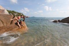 Langhaariges Mädchen und Kerl sitzen auf großem Stein am Hintergrund von azurblauem Meer Lizenzfreie Stockfotografie