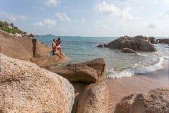 Langhaariges Mädchen und Kerl sitzen auf großem Stein am Hintergrund von azurblauem Meer Stockbild