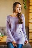 Langharig meisje met vlecht, in lange purpere sweater en jeans royalty-vrije stock afbeelding