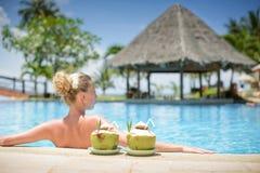 Langharige blondevrouw met bloem in haar in bikini op tropische pool Stock Afbeeldingen