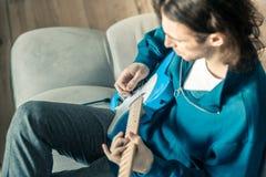 Langharige jonge musicus met golvend haar die aandachtig de gitaar spelen royalty-vrije stock afbeelding