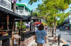 Langharige jongen die onderaan stoep voorbij resturants en tropische bomen met fietsruiters en andere toeristen in Key West lopen stock foto's