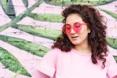 Langharige krullende donkerbruine vrouw in roze kleding en roze glazen stock foto's