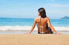 Langharige meisjeszitting op een overzees strand Royalty-vrije Stock Afbeeldingen
