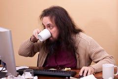Langharige mens bij vuil bureau Stock Afbeelding