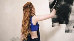 Langharige mooie vrouw die de ruimte verfraaien die rol en zwarte verf gebruiken Achter mening stock videobeelden