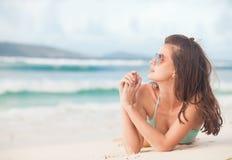 Langharige vrouw in bikini die op tropisch strand liggen stock foto's