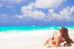Langharige vrouw met bloem in haar in bikini bij tropisch strand stock foto