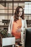 Langharige zwangere vrouw die haar dingen van het kabinet verzamelen stock foto's