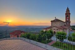 Langhe教会和小山在日落的。 库存照片