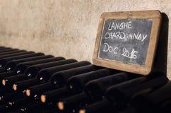 Langhe chardonnay flaskor som åldras i en källare arkivfoto