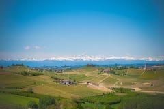 Langhe con las montañas de las montañas y las uvas verdes con el cielo clowdy azul imágenes de archivo libres de regalías
