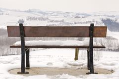 Langhe winter snowy view, behind a bench. Color image. Winter view of vineyards in the hilly region of Langhe in the southern area of Piemonte Region, Northern Royalty Free Stock Images
