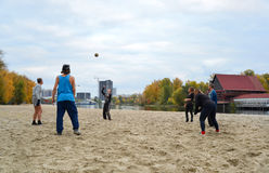 Langjährige Freunde, die Strandvolleyball am Herbsttag spielen Stockfotos