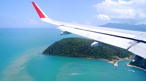 LANGKAWI, MALÁSIA - 4 de abril de 2015: Vista da janela do avião com asa de uma aterrissagem de avião em uma ilha tropical Imagens de Stock Royalty Free