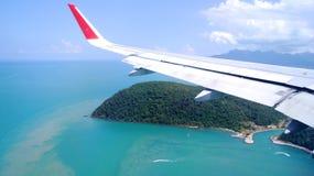 LANGKAWI, MALEISIË - 4 APRIL 2015: Mening van vliegtuigvenster met vleugel van een vliegtuig die op een tropisch eiland landen Royalty-vrije Stock Afbeeldingen