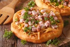 Langos ha fritto nel grasso bollente con il primo piano del prosciutto e del formaggio orizzontale Fotografia Stock