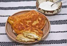 Langos (pasta frita - buñuelos) llenó de queso salado Imagenes de archivo